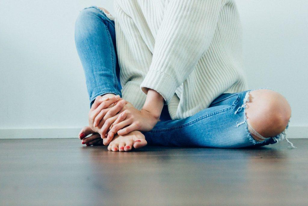 クラッシュジーンスを履く女性