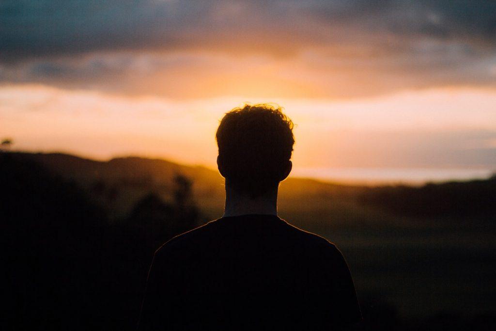 夕日を見つめる男性