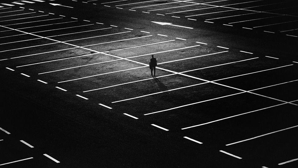 暗い駐車場を歩く男性