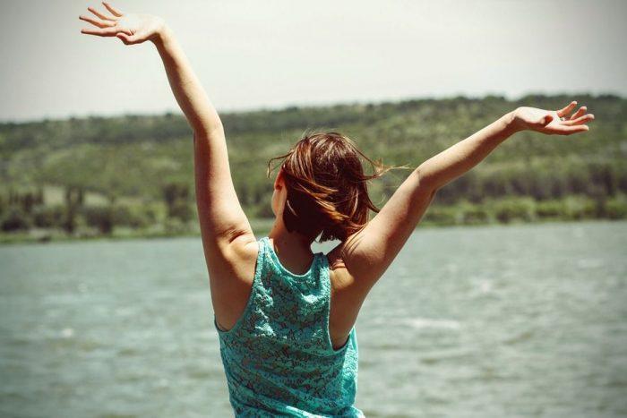 手を上げて喜ぶ女性