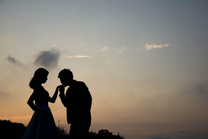 彼女の手にキスをする男性