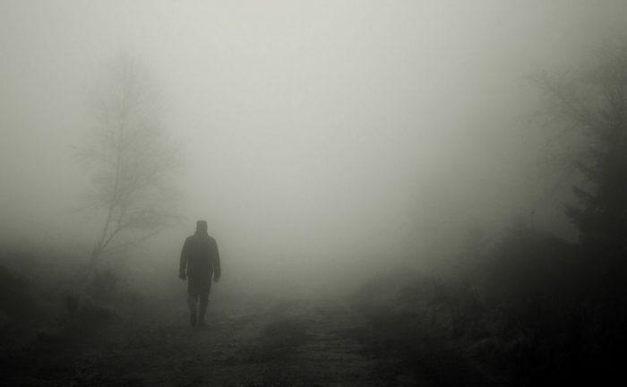 霧の中を歩く男性